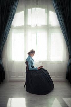 Ildiko Neer Victorian woman sitting and reading by window