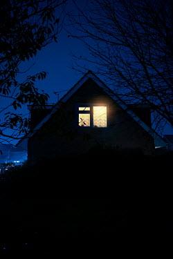 Lee Avison LIGHT IN BEDROOM OF MODERN HOUSE AT NIGHT Houses