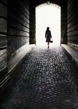 Nikaa WOMAN WALKING ON COBBLED STREET IN TUNNEL Women