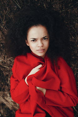 Irina Orwald BLACK WOMAN IN RED COAT LYING ON GRASS Women
