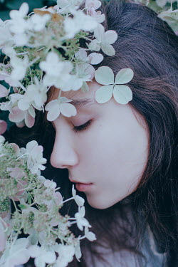 Irina Orwald BRUNETTE GIRL WITH CLOSED EYES AND FLOWERS OUTDOORS Women