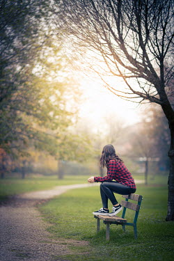 Paolo Martinez Young woman sitting on park bench