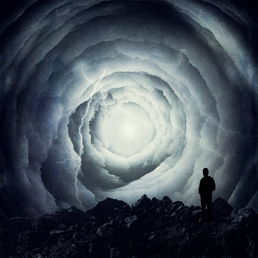 Dirk Wustenhagen Silhouette of man standing on rocks under storm clouds