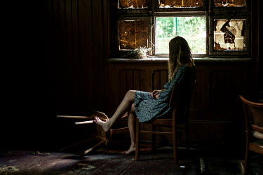 Elisabeth Mochner Woman sitting on wooden chair in abandoned house