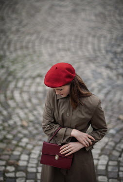 Nikaa Woman in red beret and coat on cobbled street