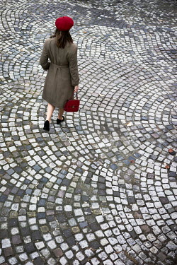 Nikaa Woman in red beret and coat walking on cobbled street