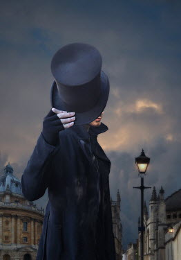 Lyn Randle Man holding top hat in city