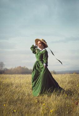 Joanna Czogala Victorian woman in green dress and hat standing in field