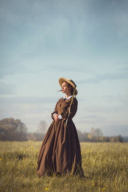 Joanna Czogala Victorian woman in brown dress standing in field