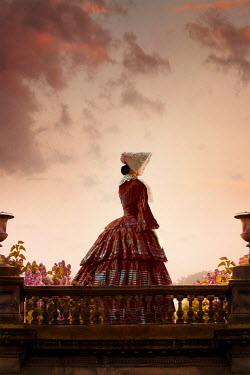 Lee Avison Victorian woman in bussle dress and bonnet standing behind a balustrade