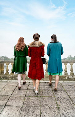 Stephen Mulcahey Young women in vintage coats walking on balcony