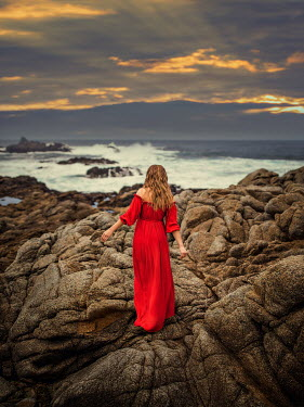 Lilia Alvarado Woman in red dress walking on rocks