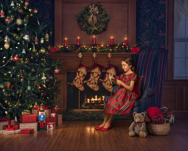 Lilia Alvarado Girl reading by Christmas tree and fireplace