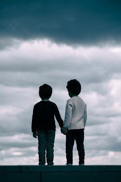 Mohamad Itani Boys holding hands under clouds