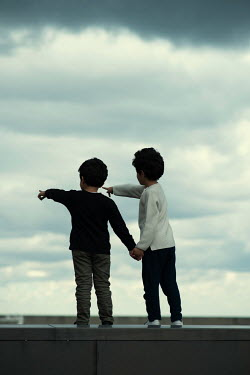Mohamad Itani Boys holding hands and pointing under clouds