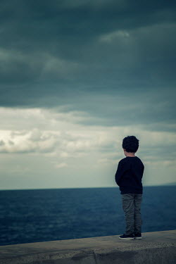 Mohamad Itani Boy standing on wall by sea