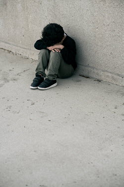 Mohamad Itani Boy sitting and crying by concrete wall