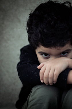 Mohamad Itani Shy boy sitting by concrete wall
