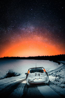 Magdalena Russocka car on country road with glow and starry sky at night