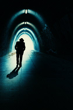 Magdalena Russocka silhouette of retro man wearing fedora hat walking in tunnel