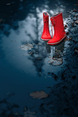 Magdalena Russocka Child's red Wellington boots abandoned in puddle