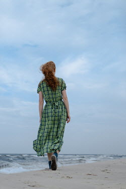 Magdalena Russocka woman in gingham dress walking on beach