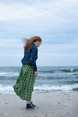 Magdalena Russocka woman in gingham dress and denim jacket standing on beach