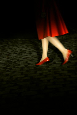 Ute Klaphake Legs of woman in red high heels walking on cobbled street