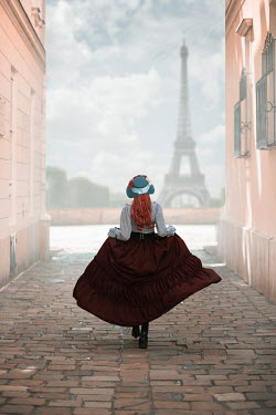 Ildiko Neer Historical woman running on cobbled street in Paris