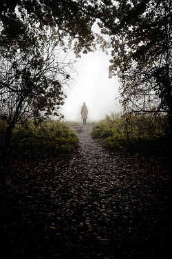 Esme Mai WOMAN STANDING ON FOGGY COUNTRY PATH Women