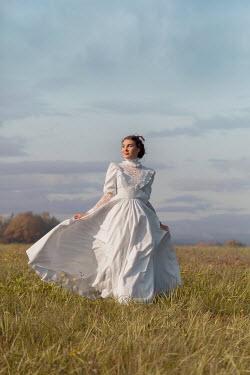 Joanna Czogala WOMAN WITH WHITE GOWN IN BREEZY COUNTRYSIDE Women