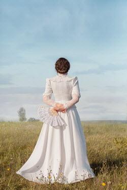 Joanna Czogala WOMAN IN WHITE WITH FAN STANDING IN COUNTRYSIDE Women