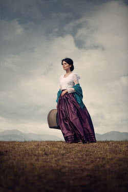 Magdalena Russocka historical woman with suitcase standing in field