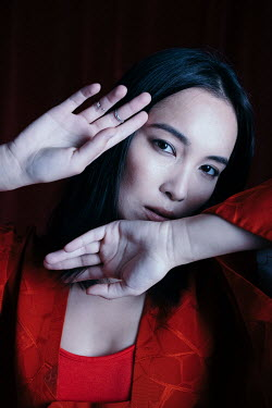 Marta Syrko ASIAN WOMAN IN RED WITH RAISED HANDS Women