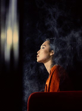 Marta Syrko ASIAN WOMAN SITTING INDOORS WITH SMOKE Women