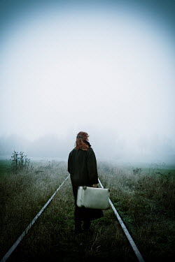 Carmen Spitznagel WOMAN CARRYING SUITCASE ON RAILWAY IN COUNTRYSIDE Women