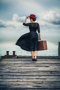 Marie Carr RETRO WOMAN CARRYING SUITCASE ON JETTY BY SEA Women