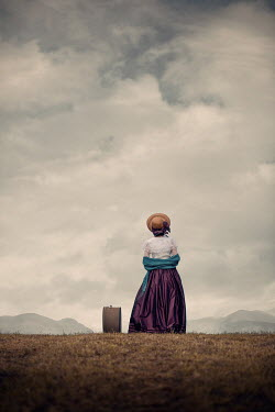 Magdalena Russocka historical woman with suitcase wearing bonnet standing in field