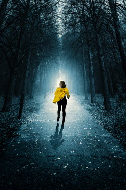 Magdalena Russocka modern woman wearing yellow jacket running in woods
