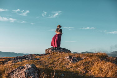 Mary Wethey WOMAN STANDING ON ROCK WATCHING LANDSCAPE Women
