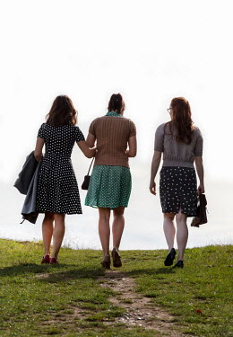 Stephen Mulcahey THREE GIRLS IN SUMMER DRESSES WALKING IN FIELD Groups/Crowds