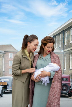 Stephen Mulcahey TWO RETRO WOMEN WITH BABY IN URBAN STREET Women