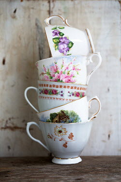 Alison Archinuk STACK OF FLORAL TEACUPS ON TABLE Miscellaneous Objects