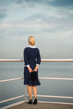 Joanna Czogala BLONDE RETRO WOMAN STANDING BY RAILINGS AND SEA Women