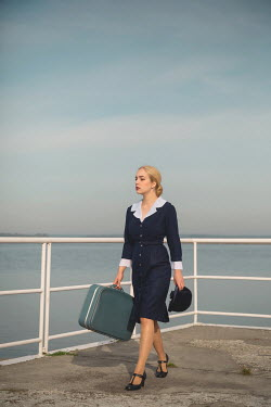 Joanna Czogala BLONDE RETRO WOMAN CARRYING SUITCASE BY WATER Women