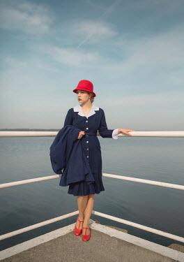 Joanna Czogala BLONDE RETRO WOMAN STANDING BY RAILINGS AND SEA Women
