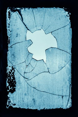 Magdalena Russocka hole in broken window pane glass with sky