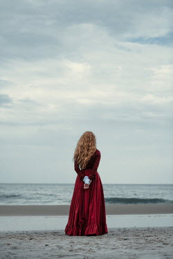 Magdalena Russocka historical woman in red dress standing on sandy beach Women