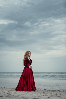 Magdalena Russocka historical woman in red dress standing on sandy beach