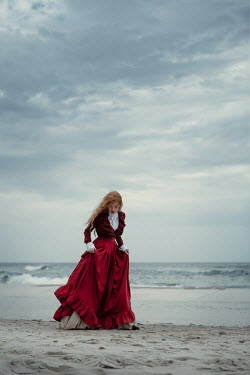 Magdalena Russocka historical woman in red dress walking on sandy beach